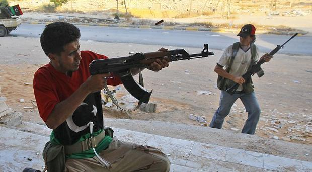 Rebel fighters take position during an attack in Tripoli (AP)