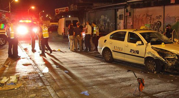 Policemen gather at a site where a Palestinian man crashed a car into a crowd of people and stabbed others near a nightclub in Tel Aviv (AP)