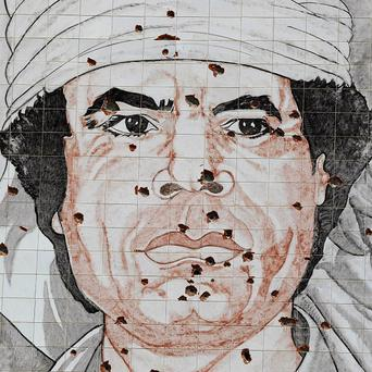 A giant portrait of Gaddafi is riddled with bullets (AP)
