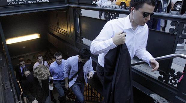 Commuters exit the Wall Street subway station in New York as public transport services resumed after Hurricane Irene (AP)