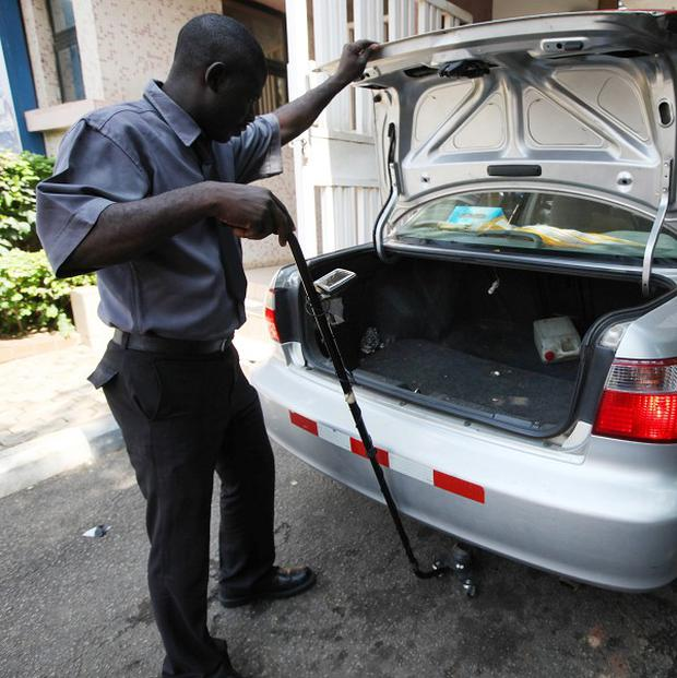 A security guard examines a car at Wuse Market in Abuja, Nigeria (AP)