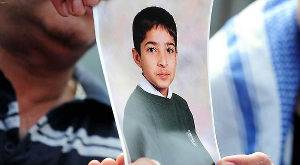 A mourner holds a picture of Haroon Jahan, who died after being knocked down by a car amid rioting in Birmingham
