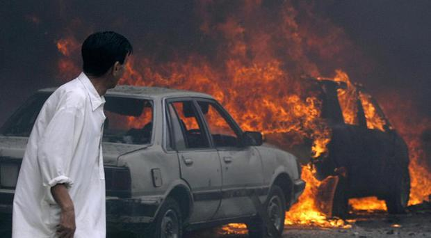 A man looks at burning cars in Quetta, Pakistan (AP)