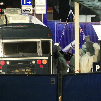 Police carry away a body from the scene after the two US servicemen were gunned down at Frankfurt airport(AP)