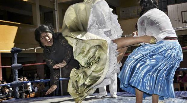 Picture by Daniele Tamagni, Italy. 2nd Prize Arts and Entertainment Stories. The Flying Cholitas, Bolivia. Lucha libre (Bolivian wrestling) is one of the most popular sports in the country. Women wrestlers are known as cholitas and have in the last ten years become popular in the sport. Here, Carmen Rosa and Yulia la Pacena perform in a benefit show to raise money for the bathrooms of a school in La Paz, Bolivia. <br/> <b>Daniele Tamagni</b>