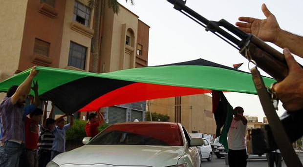 Libyan residents of Jamal Goubtan district in Tripoli hold a giant former Libyan flag for cars to drive under (AP)