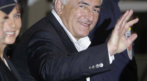 Dominique Strauss-Kahn, former head of the International Monetary Fund, waves upon his arrival back in France (AP)