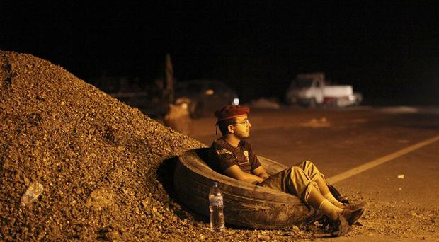 A rebel fighter rests at a checkpoint between Tarhouna and Bani Walid, in Libya (AP)