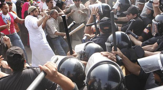 Egyptians protesting against ousted president Hosni Mubarak clash with riot police outside the court in Cairo where he is due to appear (AP)