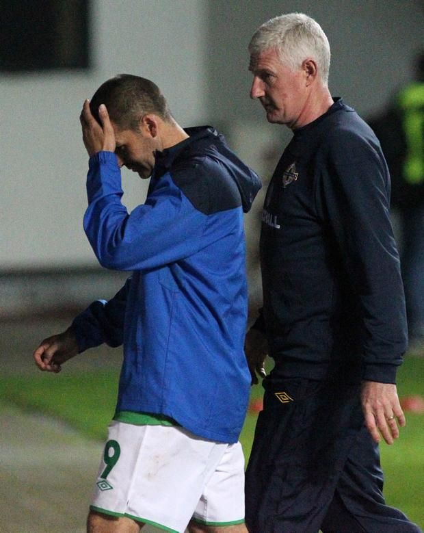 Northern Ireland manager Nigel Worthington walks off at full time with striker David Healy