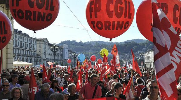 Strikers march through central Turin, Italy, as part of a national day of action in protest at austerity cuts(AP)
