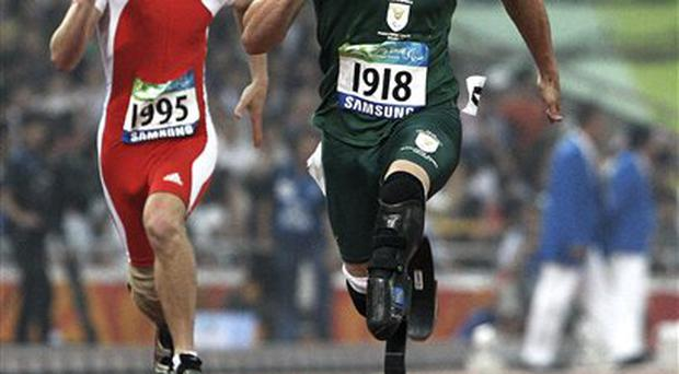 Oscar Pistorius, right, is followed by Christoph Bausch of Switzerland as they compete in the Men's 100m T44 during the Beijing Paralympic Games