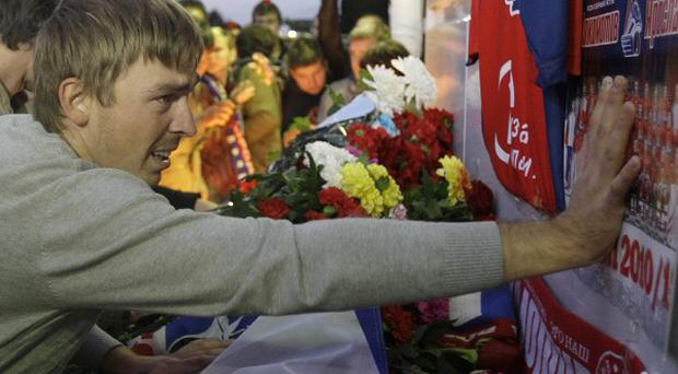 Fans of the Lokomotiv ice hockey team lay flowers at the Lokomotiv Arena to pay tribute to players killed in a plane crash in Yaroslavl, Russia (AP)