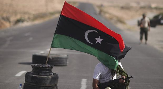 A rebel fighter at a checkpoint in Libya as the hunt for Gaddafi continues (AP)
