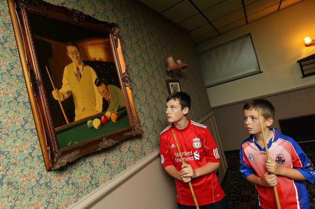 Daniel Nixon and Calum Devlin beside a portrait of Dennis Taylor in Gervin's Snooker Hall