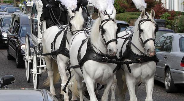 The coffin of Mark Duggan is carried by horse drawn carriage on its way to the New Testament Church of God in Wood Green, north London