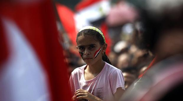 An Egyptian girl has a face painting with colors of the national flag as she attends a protest at Tahrir Square in Cairo (AP Photo/Khalil Hamra)