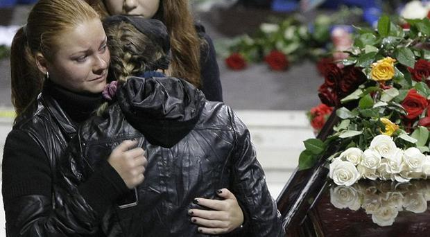 Mourners console each other at the funeral of the victims of a plane crash in Russia (AP)