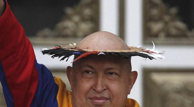 Venezuela's President Hugo Chavez raises his fist into the air after being presented with a 'healing hat' (AP)
