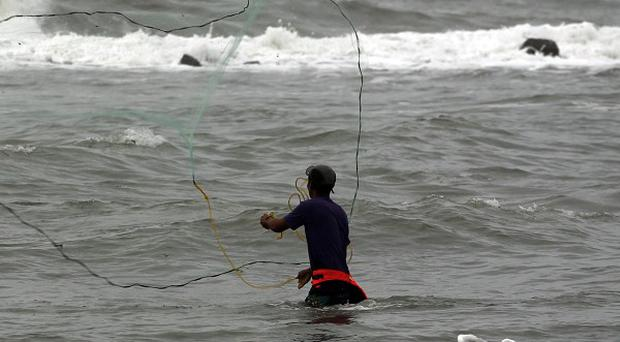 A fisherman casts his net into the waters off Mexicoas Tropical Storm Nate approaches (AP)