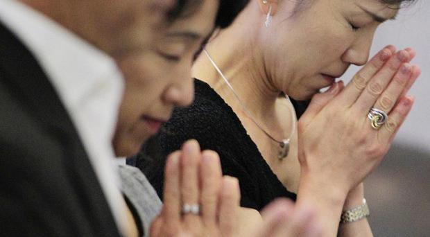 Japanese families pray during a memorial service to mark the 10th anniversary of the September 11 terrorist attacks (AP)