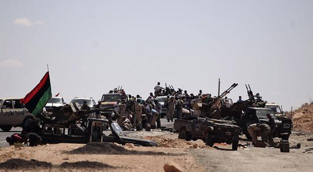 Former rebel soldiers gather at the frontline near Bani Walid ready for a final assault on one of the Gaddafi regime's last remaining bastions (AP)