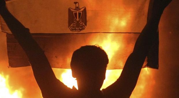 A protester holds the Egyptian national flag as a fire rages outside the building housing the Israeli Embassy in Cairo (AP)