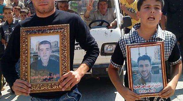 Anti-Syrian President Bashar Assad protesters hold portraits for their dead relatives killed in recent violence (AP)