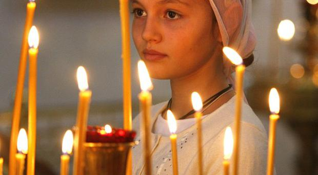 A girl attends an Orthodox service at St Catherine's in Moscow in remembrance of the victims of the September 11 terror attacks (AP)