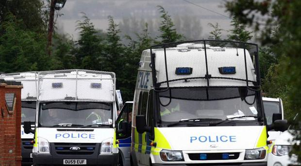 Police vans at the Greenacre caravan site in Leighton Buzzard, where five residents were arrested on suspicion of slavery offences