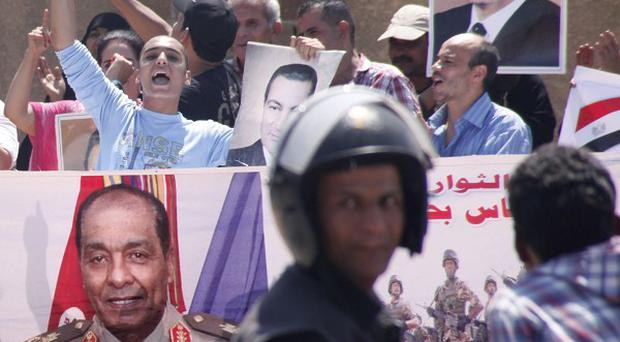 Egyptian pro-Mubarak supporters display his posters and a giant image of Field Marshal Mohammed Hussein Tantawi outside court in Cairo (AP)