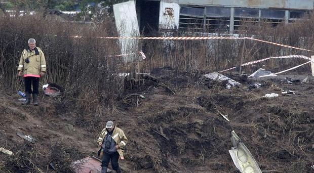 Workers collect debris of the Russian2 jet which crashed near Yaroslavl, killing 44 people including an entire ice hockey team(AP)