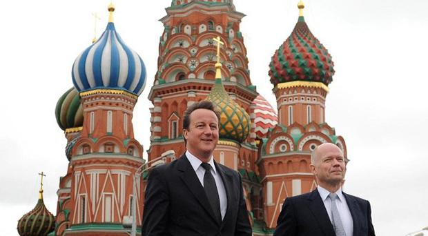 David Cameron and William Hague walk across Red Square in Moscow