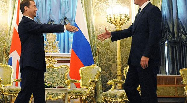 David Cameron is greeted by Russian President Dmitry Medvedev on his arrival at The Kremlin