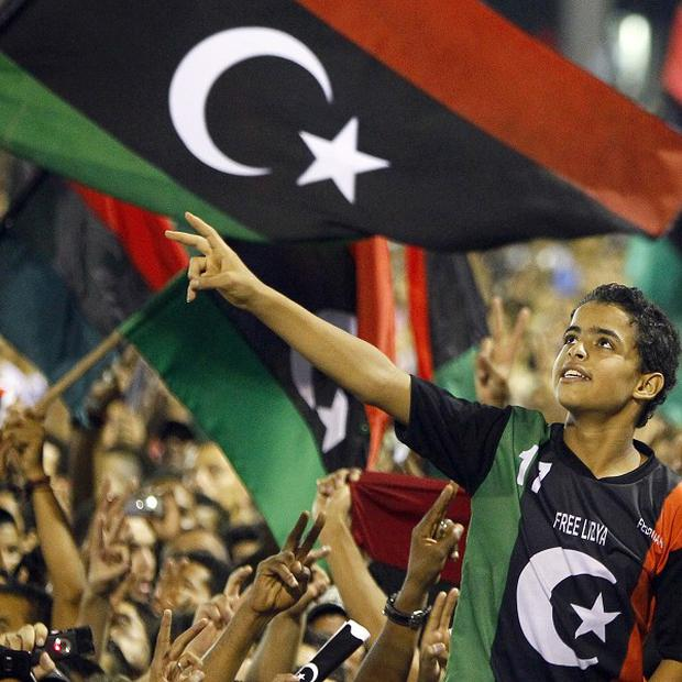 Libyan revolutionary supporters cheer at a speech by Transitional National Council chairman Mustafa Abdel Jalil in Tripoli(AP)