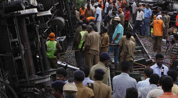 Rescue workers crowd next to the compartments of two trains after they collided near Arakkonam, southwest of Chennai, India (AP)