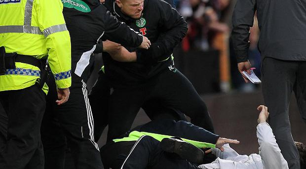 Neil Lennon is assisted after being attacked by a fan during the match between Heart of Midlothian and Celtic