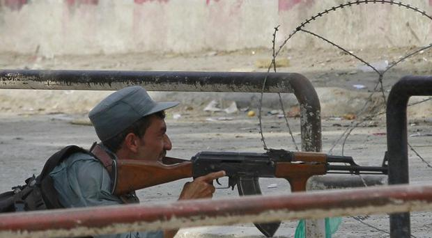 An Afghan policeman takes position near a building which was occupied by militants in Kabul (AP)