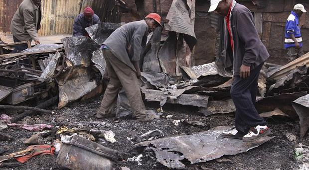 People search through the debris of their burnt-out home in Nairobi, Kenya (AP)