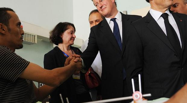 Prime Minister David Cameron and French President Nicholas Sarkozy meet patients at the Tripoli Medical Centre