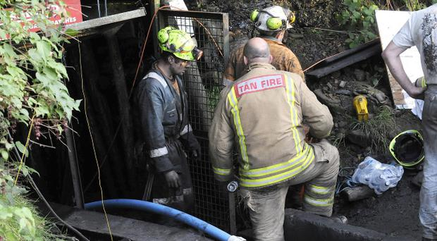 Handout photo issued by South Wales Police of emergency workers at the scene in Gleision Colliery near Swansea, South Wales, where four men are trapped following structural damage.