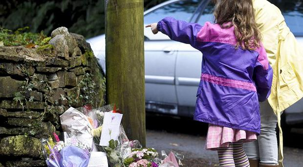 People lay floral tributes at a road junction near the Gleision Colliery near Cilybebyll in the Swansea Valley
