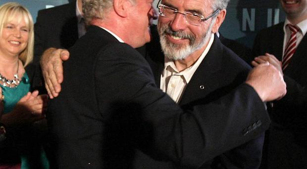 Sinn Fein President Gerry Adams congratulates Martin McGuinness as he is announced as the party's candidate for the Irish Presidency