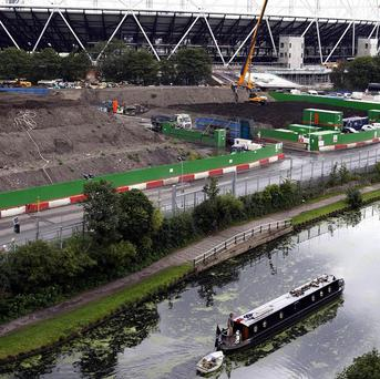 The Olympic Park under construction as a barge passes by on the River Lea