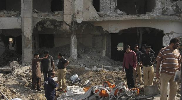Pakistani security officials examine a crater caused by a bombing in Karachi (AP)