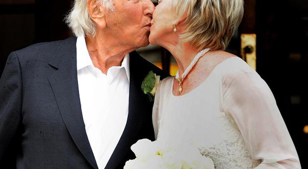 Michael Winner and wife Geraldine kiss following their wedding at Chelsea Registry Office, London