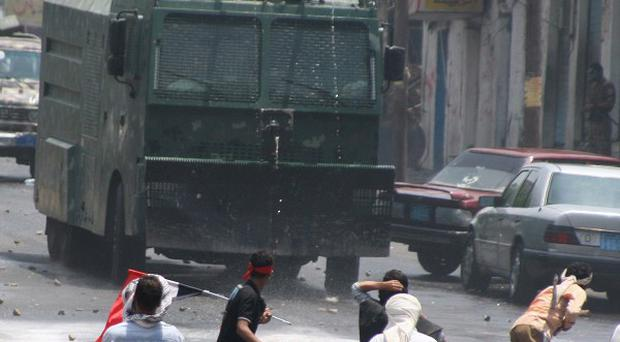 Protestors throw rocks at an anti-riot vehicle during clashes with security forces, in Taiz, Yemen(AP)