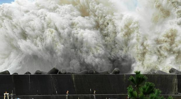 Surging waves hit against the breakwater in Udono in a port town of Kiho, Mie Prefecture, central Japan (AP)