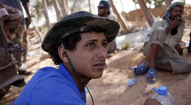 Revolutionary fighters rest near Sirte in Libya as they continue to battle pro-Gaddafi forces (AP)