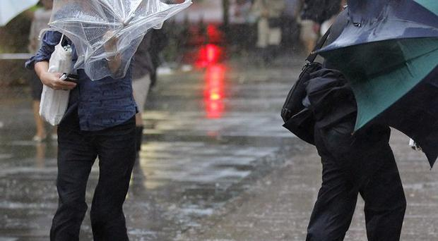 Pedestrians make their way through strong winds and rains from Typhoon Roke in Tokyo (AP/Kyodo)